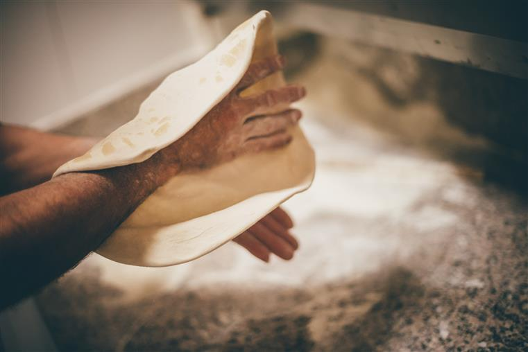 man kneading and shaping the pizza dough