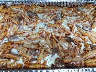 Tray of baked ziti with sausage and cheese.