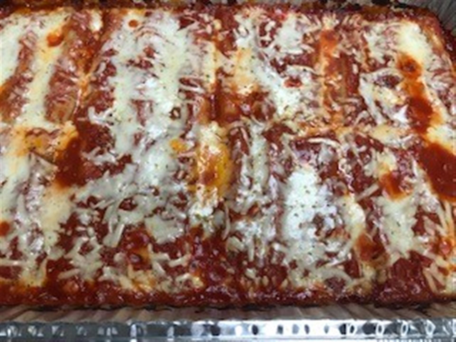 Tray of Eggplant Parmesan. Lightly breaded eggplants cooked to perfection, covered in our signature homemade marinara sauce, imported house-grated Romano cheese, and melted mozzarella