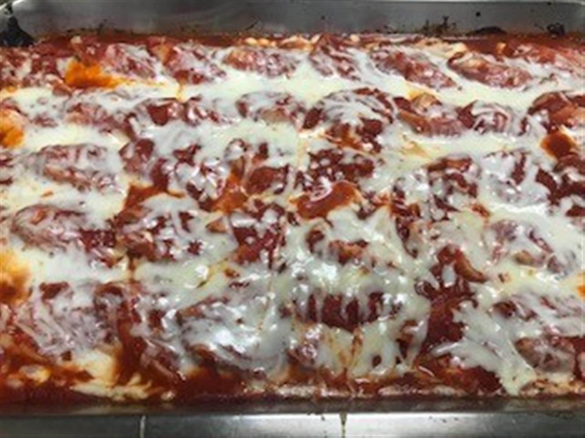 Tray of Chicken Parmesan. Breaded white-meat chicken cooked to perfection, covered in our signature homemade marinara sauce, imported house-grated Romano cheese, and melted mozzarella