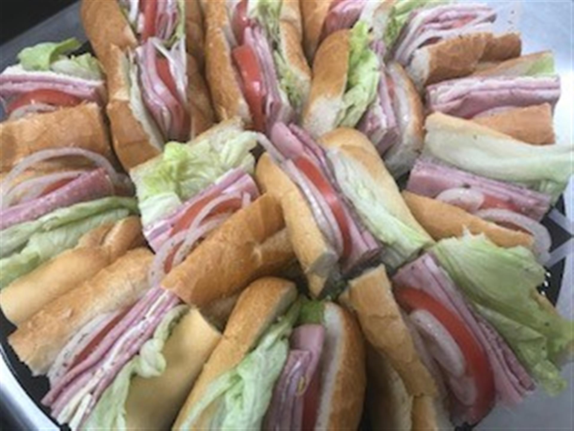 tray of sub sandwiches with ham, cheese, lettuce, tomato and onion.