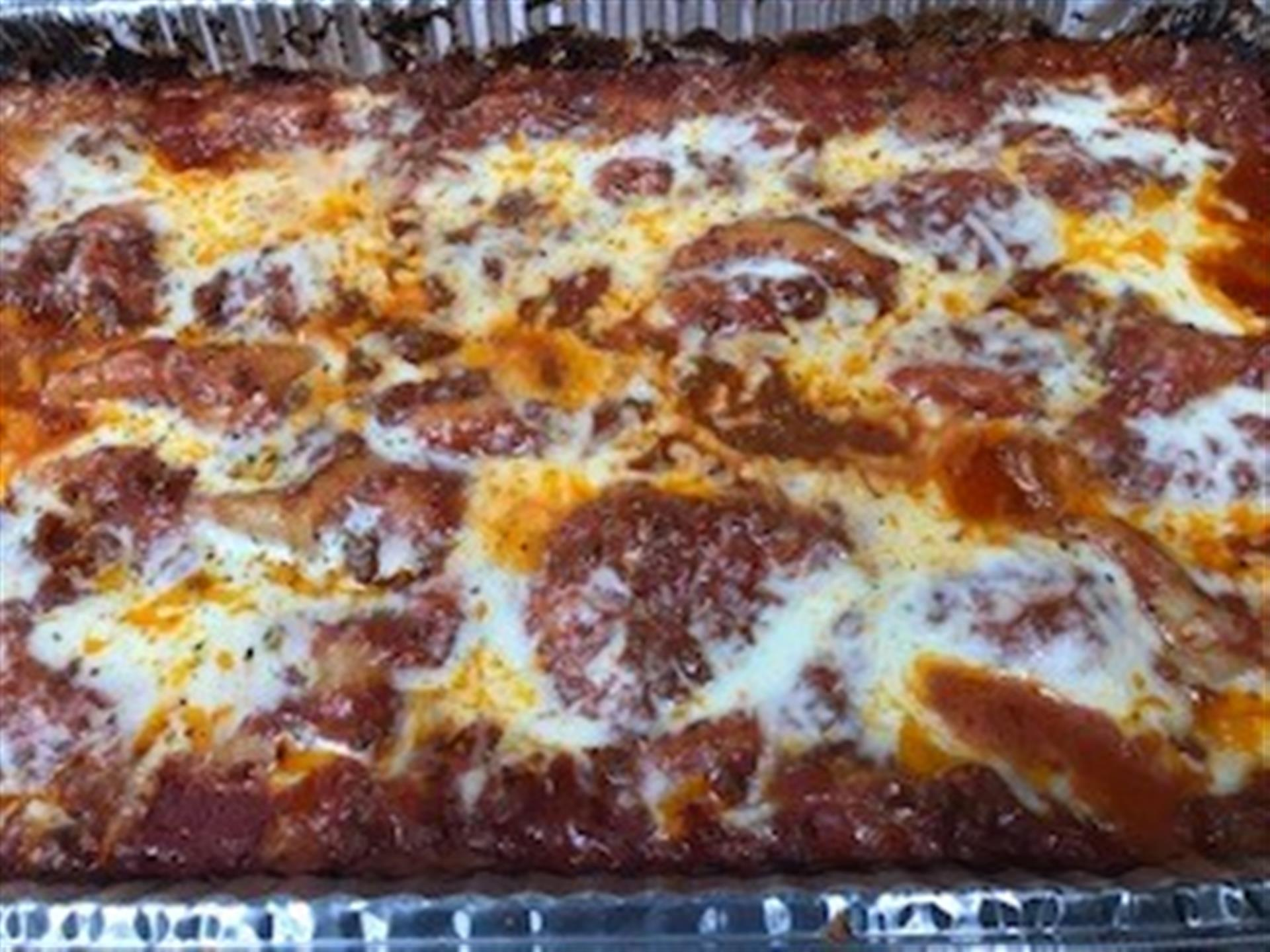 Tray of lasagna topped with cheese.