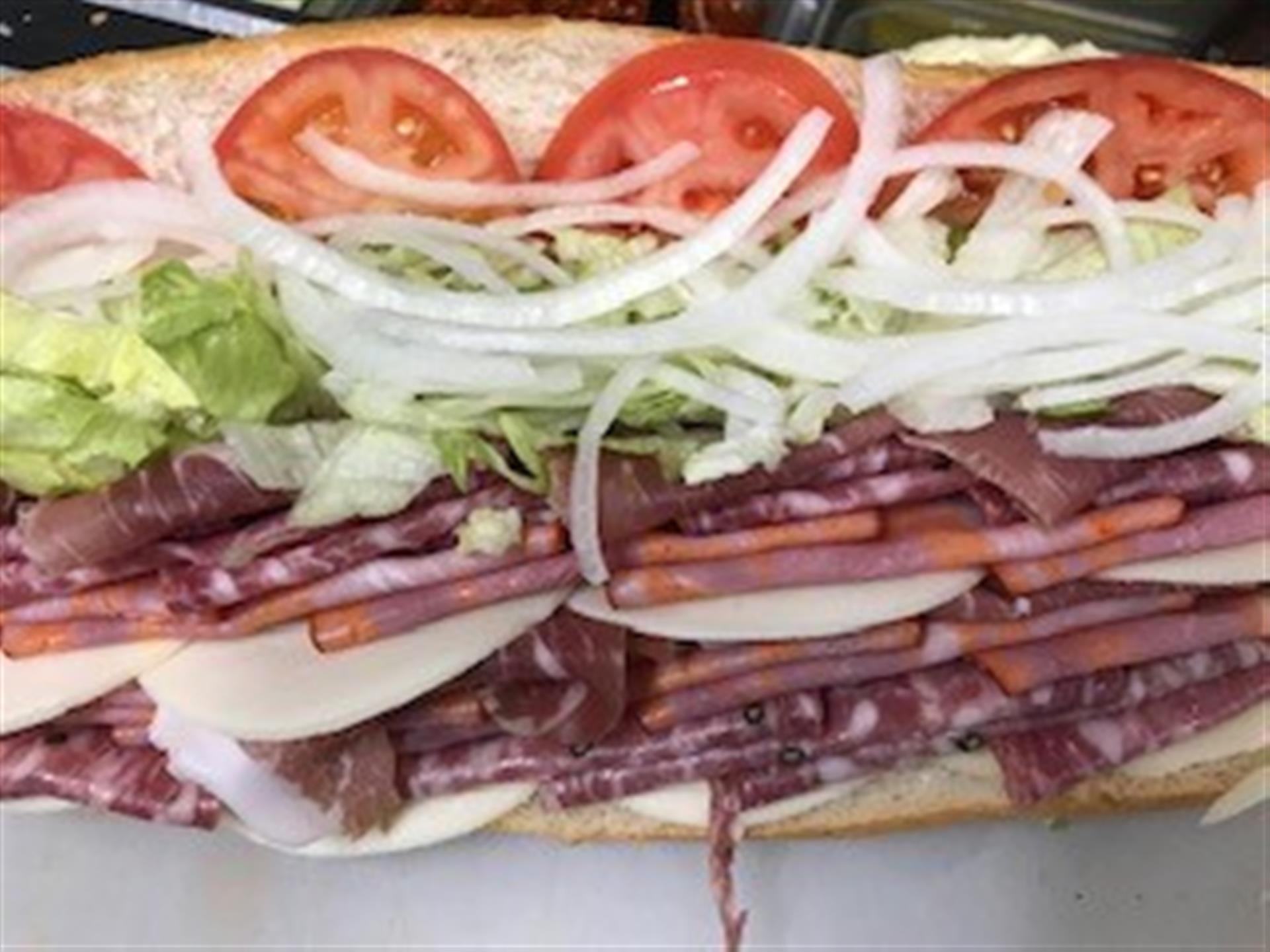 Italian sub sandwich up close with lettuce, tomato and onion.
