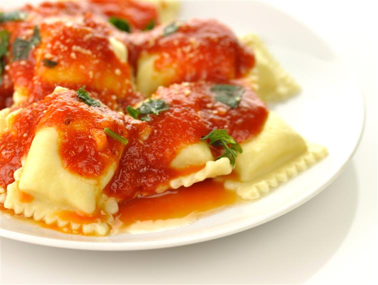 plate of ravioli garnished with basil and topped with marinara sauce