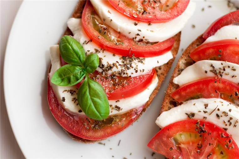 Caprese Salad. All-natural fresh mozzarella cheese, sliced ripe tomatoes, fresh basil, olive oil and seasoning.