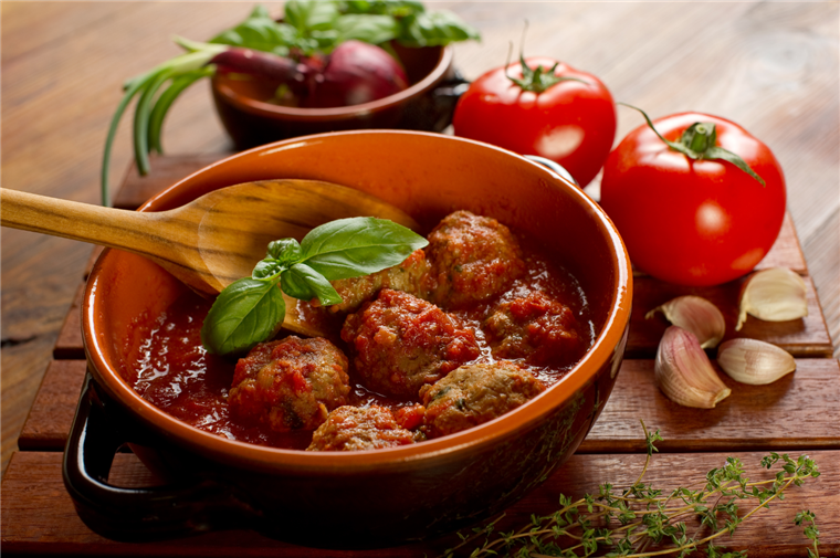 a bowl of meatballs in sauce with a wooden spoon