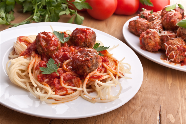 spaghetti with three meatballs on top with red sauce
