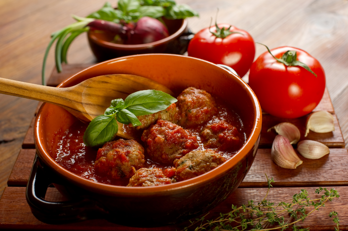 a bowl of meatballs in red sauce with a wooden spoon