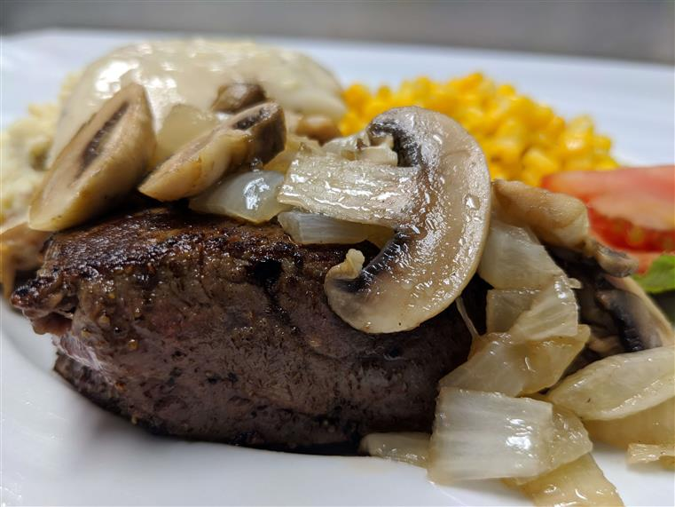 Steak topped with grilled mushrooms and onions