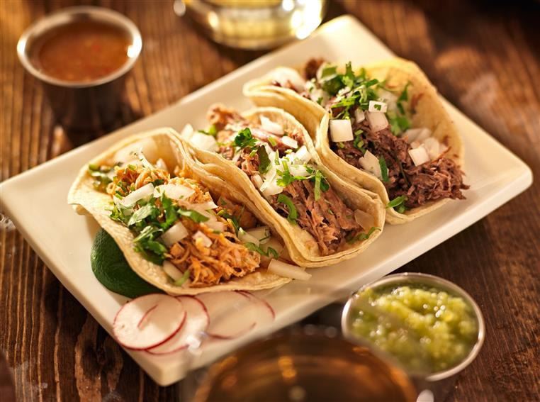 three tacos on a plate with green salsa