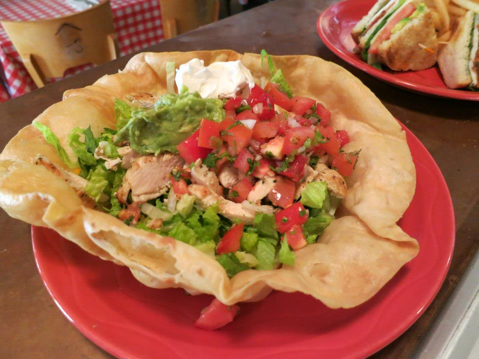 Chicken taco salad in a fried tortilla bowl with guacamole, pico de gallo and sour cream