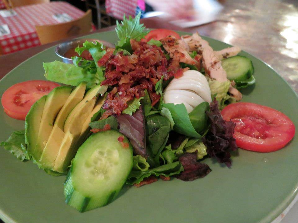 Cobb salad with hard boiled egg, sliced avocado, cucumbers, tomatoes, crumbled bacon and grilled chicken