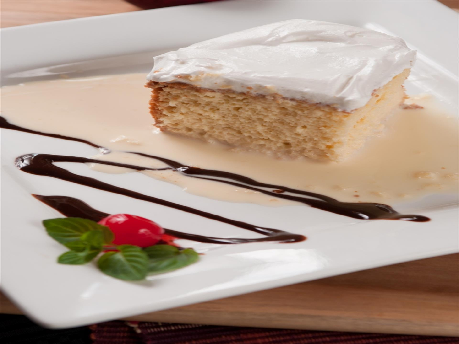 tres leches (three milks). Slice of tres leches cake with chocolate sauce.