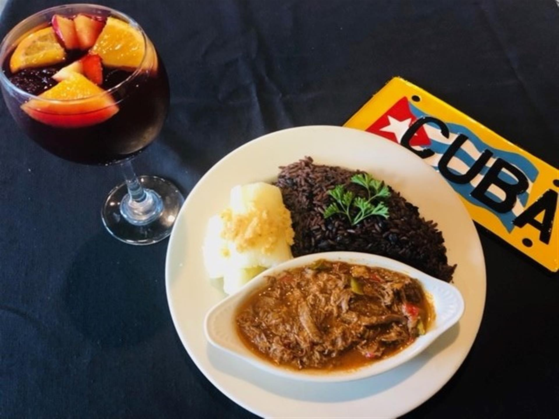 Ropa Vieja Shredded beef slow-cooked in tomato and wine sauce. cuban sign on the table beside the plate.