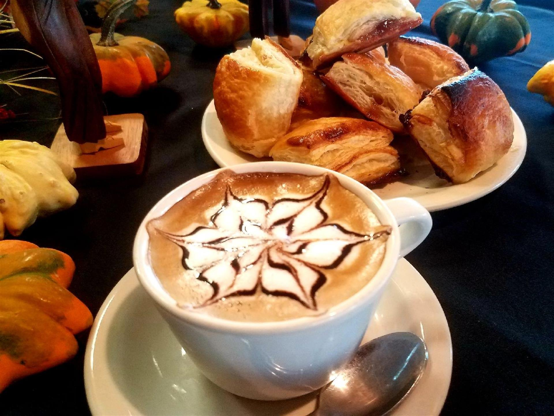 capuccino in a white cup and saucer with decorated foam. pastries on the table in the background.