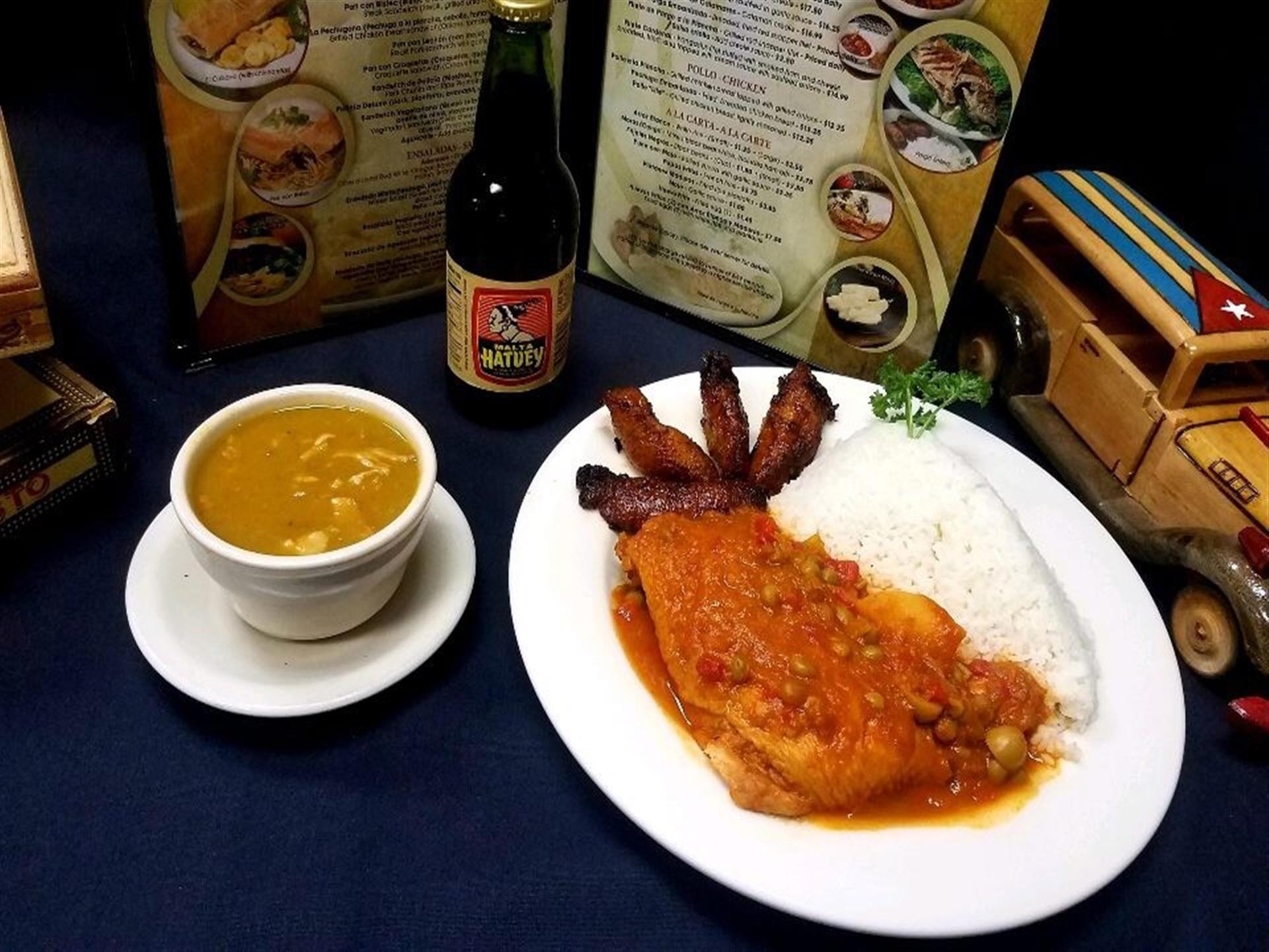 Filete de Pargo a la Plancha. Grilled red snapper filet topped with salsa criolla (creole sauce). white rice, fried plantains and cup of soup on the side.