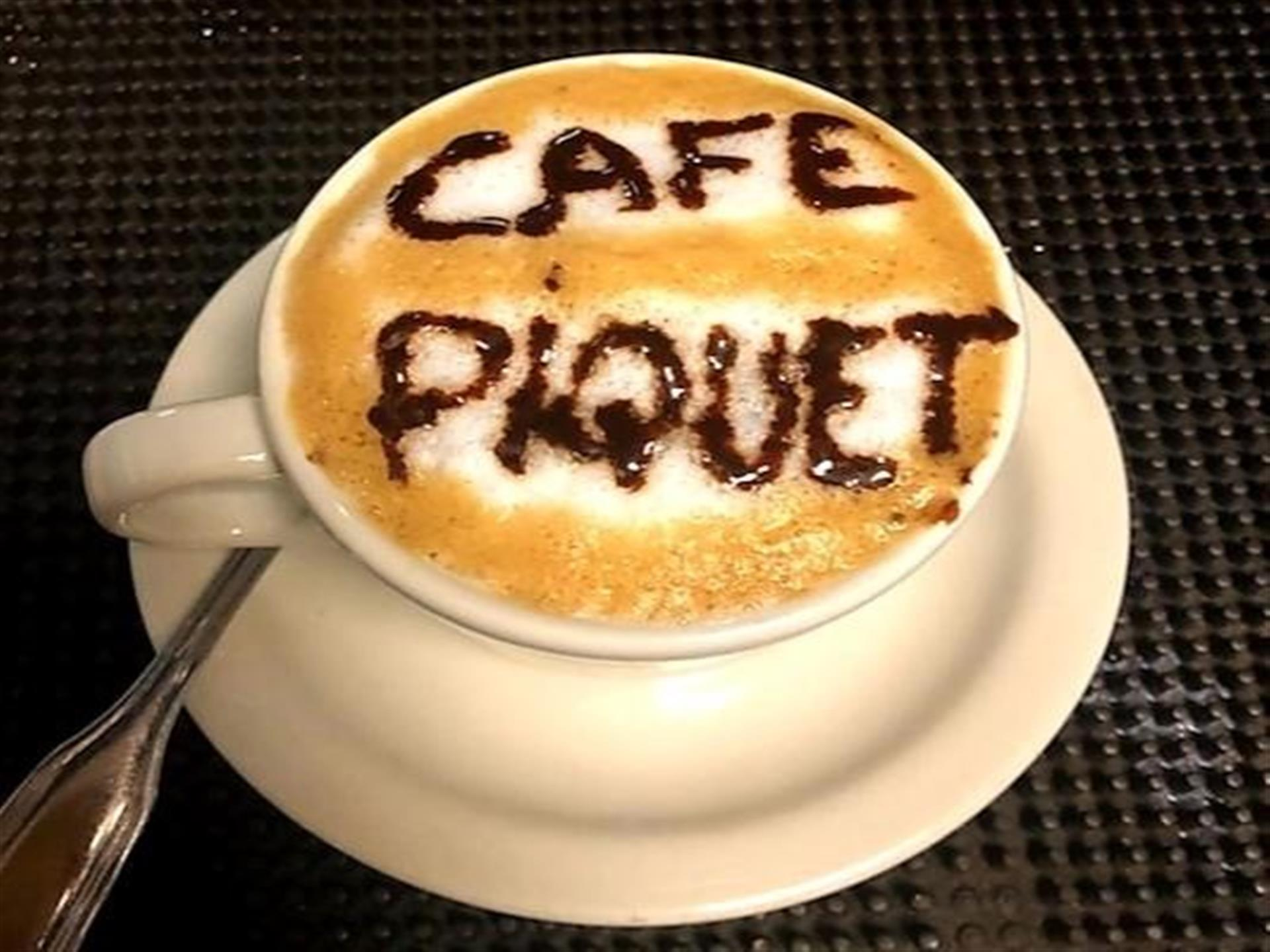 "capuccino in a white cup and saucer ""cafe piquet"" written in chocolate sauce on the foam."