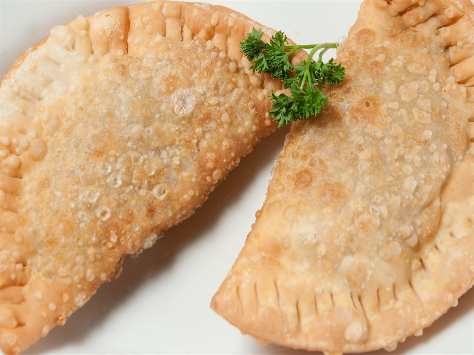 close up of two empanadas on a white plate.