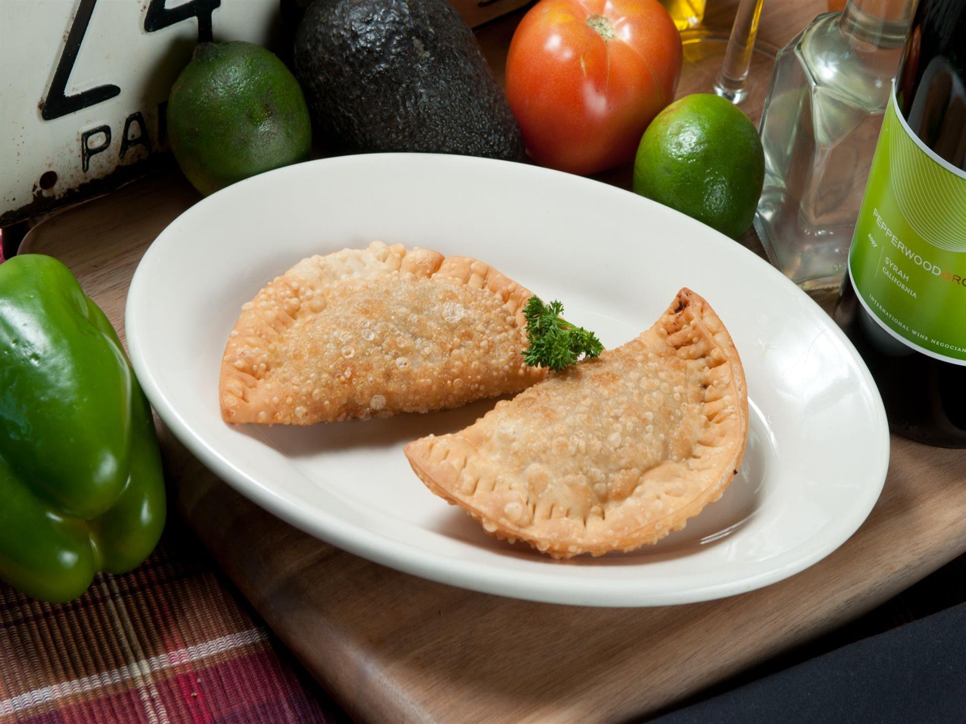 Two empanadas on a white plate. Lime, tomato, and avocado in the background.