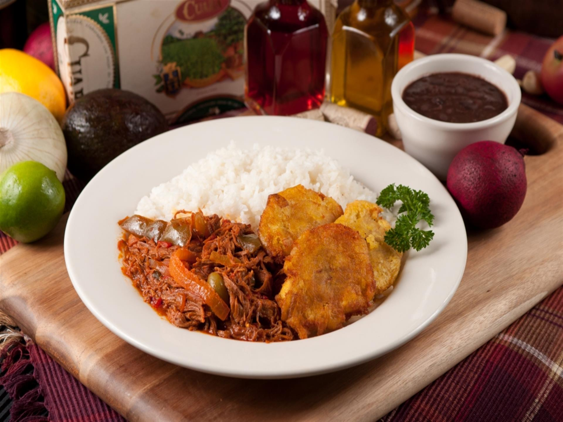 Ropa Vieja. Shredded beef slow-cooked in tomato and wine sauce. White rice and tostones on the side.