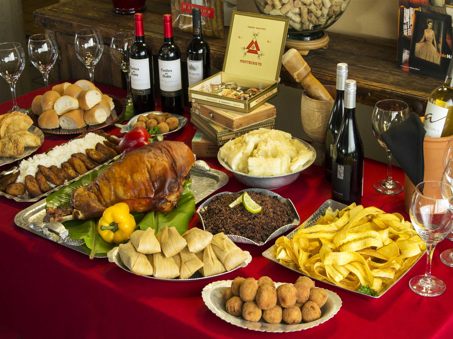 Catering display with assorted dishes of Cuban cuisine and bottles of wine with wine glasses