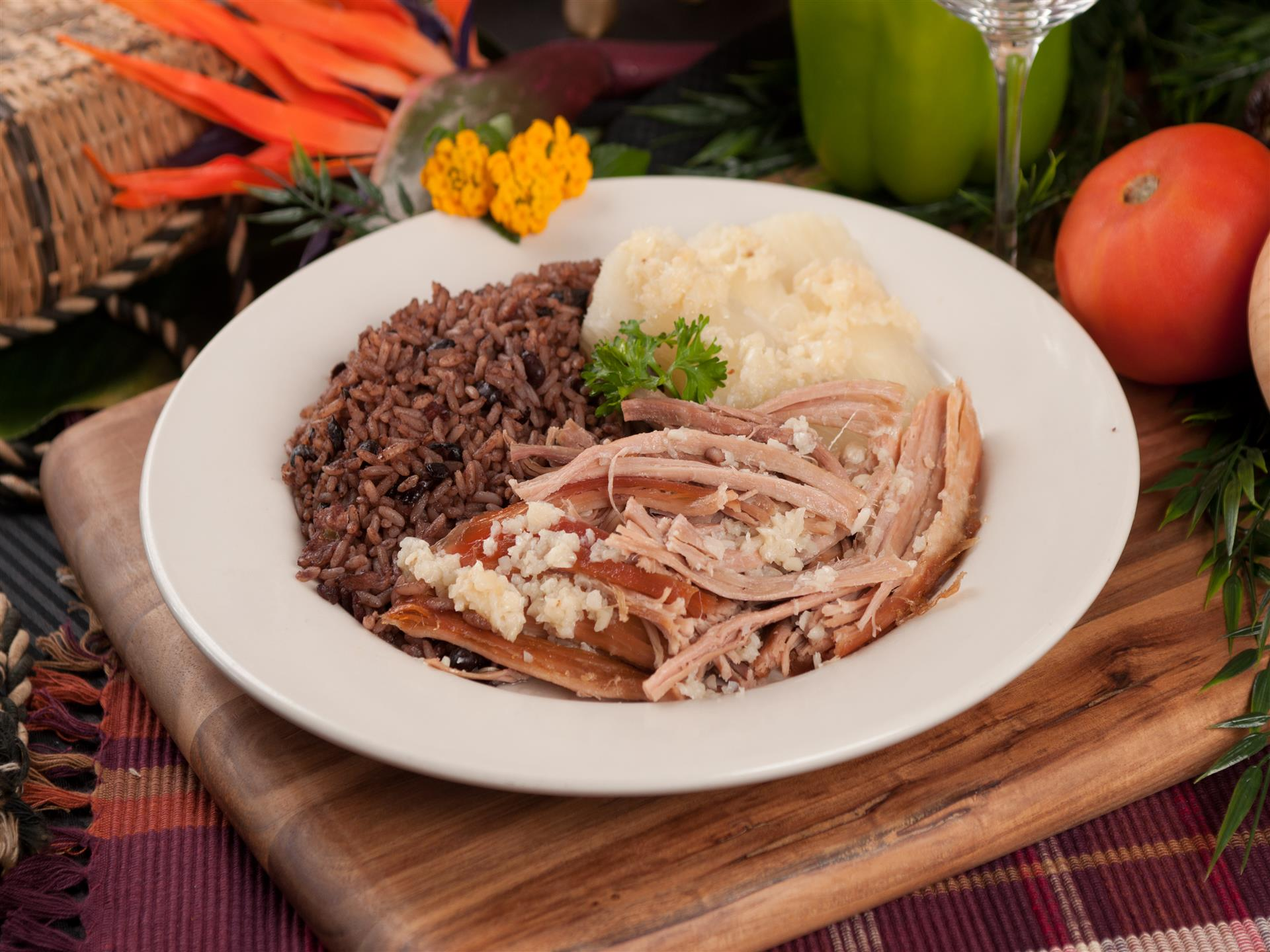 Pernil. Oven-roasted pork topped with our specialty garlic sauce. Mashed potatoes, rice and beans on the side.