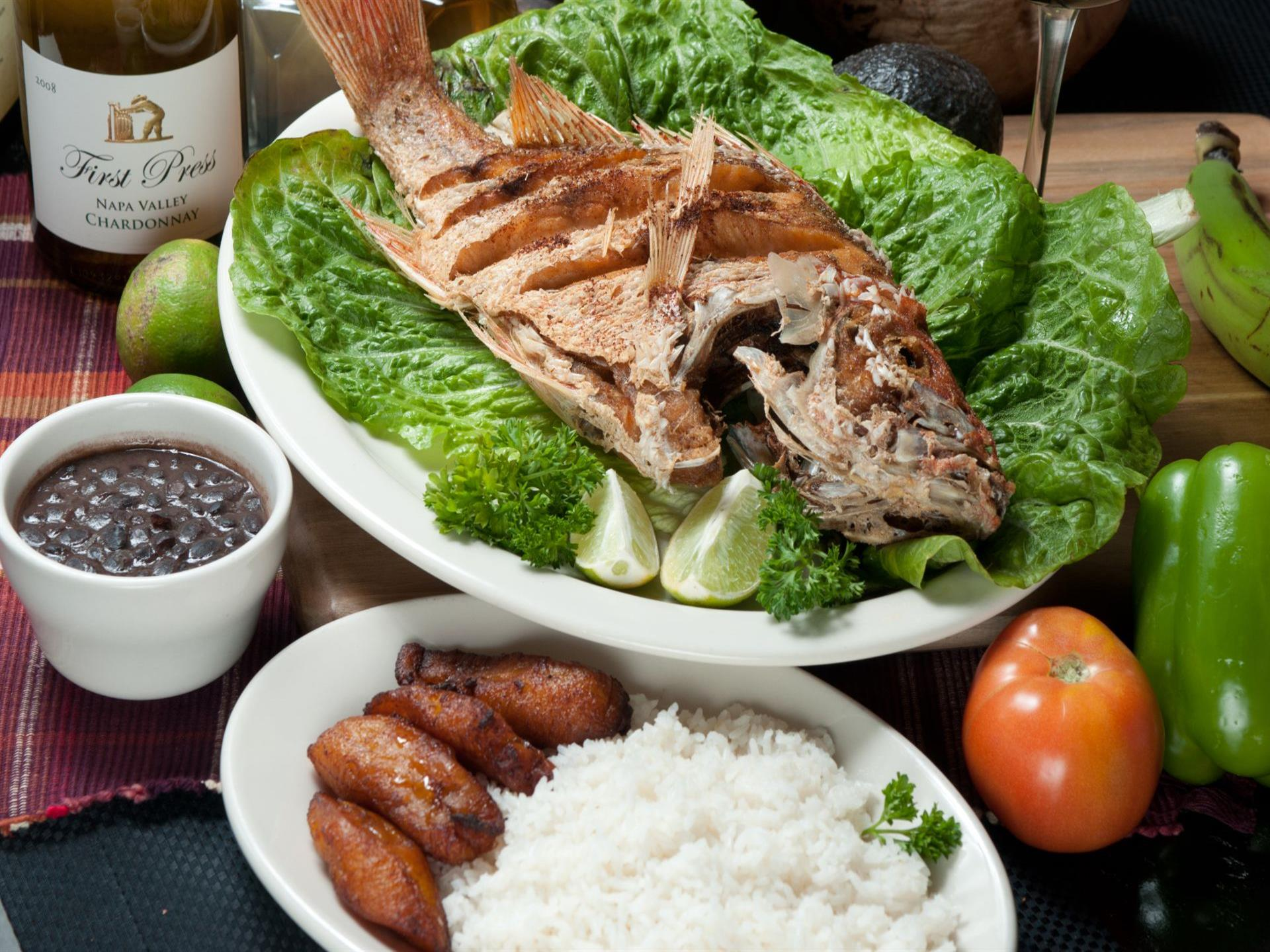 Pargo Entero Frito. Whole Fried Red Snapper on a bed of greens. White rice, fried plantains and black beans on the side. bottle of white wine, green pepper, tomato and avocado in the background.