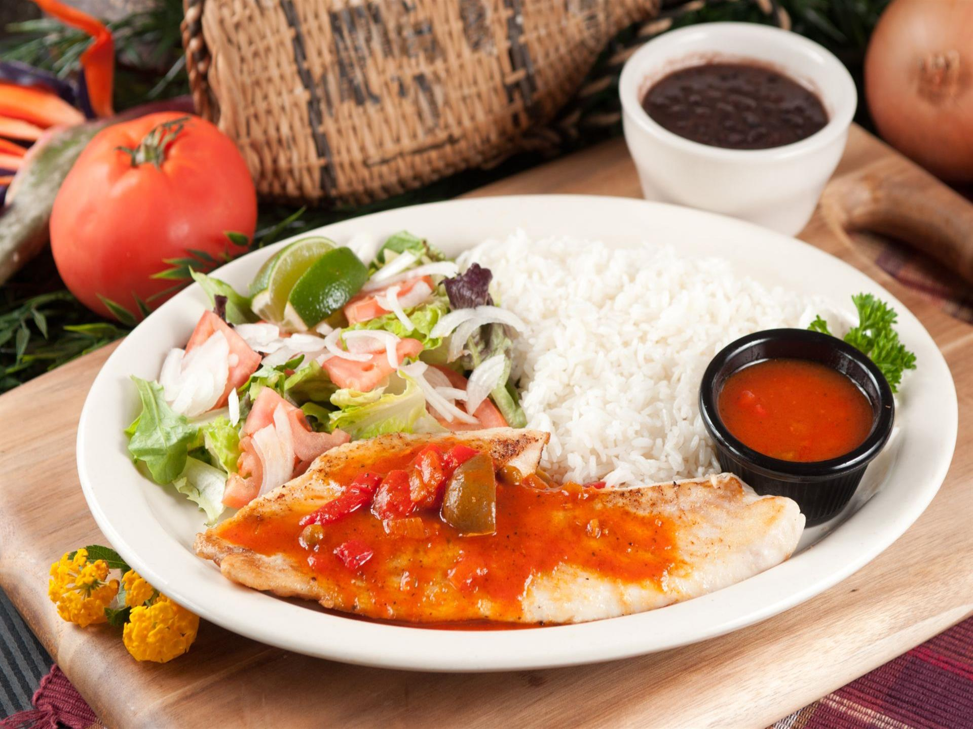 Pargo Criollo. Grilled red snapper filet with Creole sauce on top. Salad and white rice on the side. Plate placed on a wood tray. Tomato, onion and cup of black beans in the background.