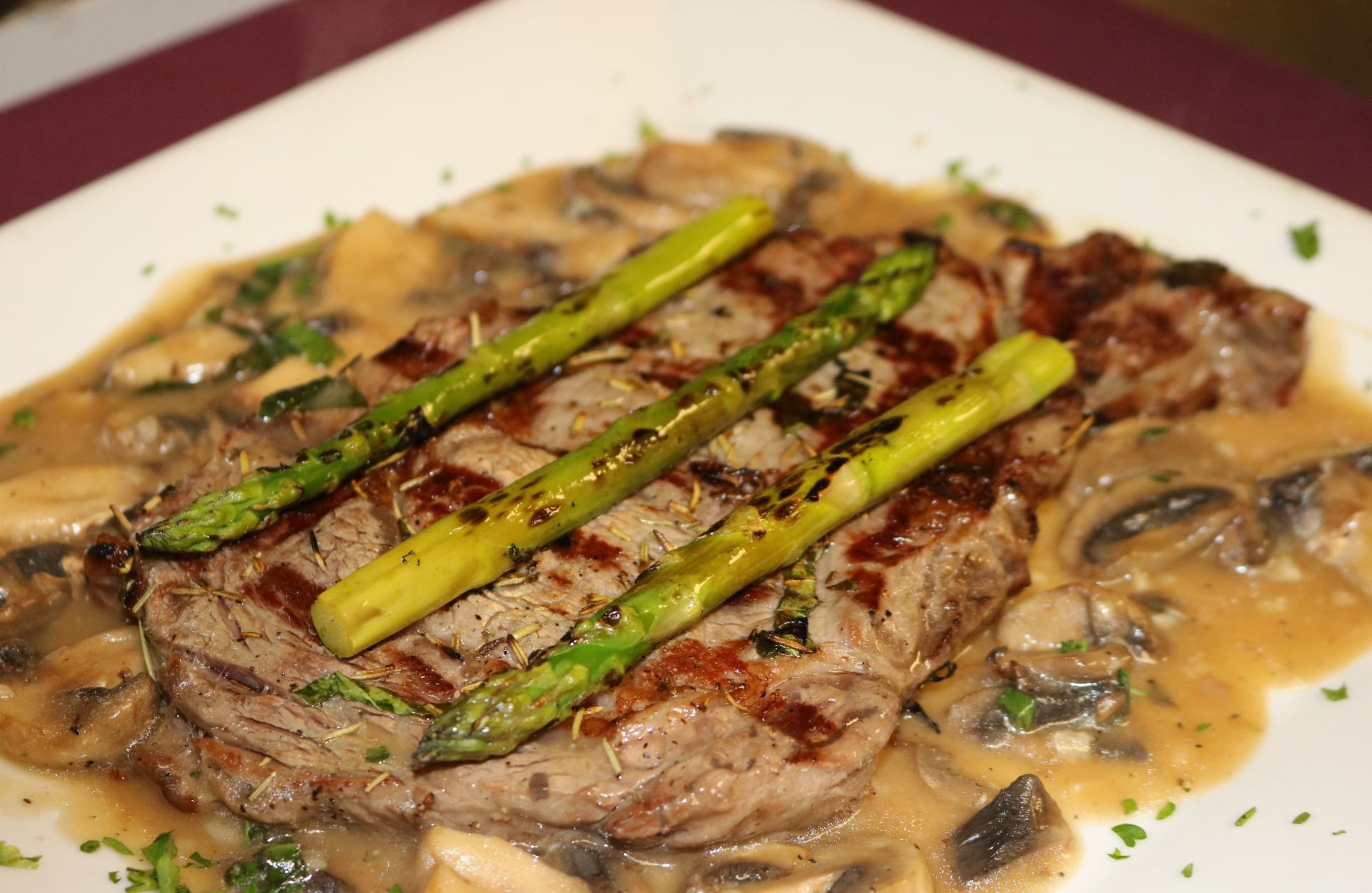 Rib-eye with grilled asparagus and mushroom in a Barolo wine reduction