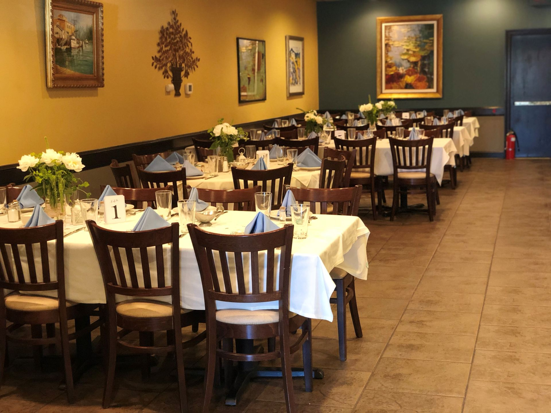Interior dining area with tables set with white table cloth and place-settings and various paintings on the walls