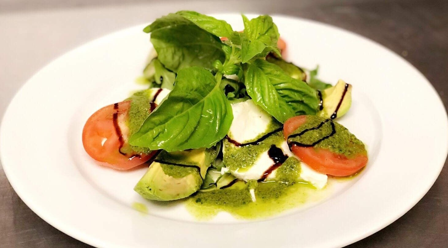 mozzarella, tomato, and basil salad with avocado and pesto sauce