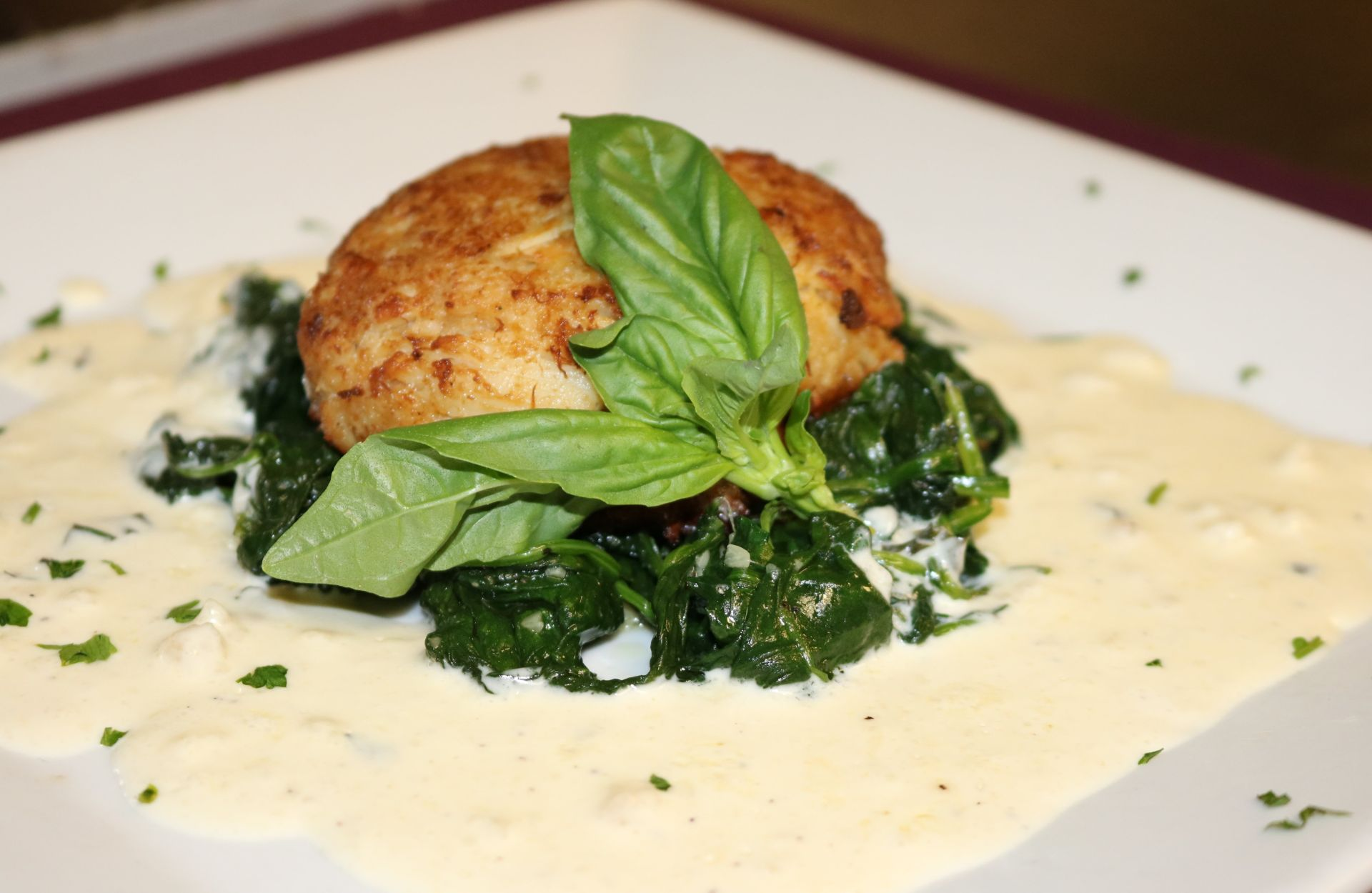 Crab cake over a bed of sauteed spinach with basil