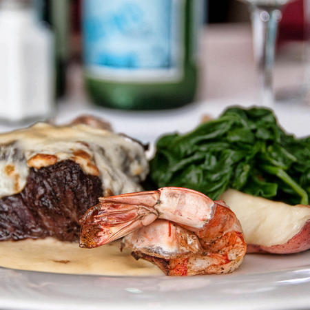 Filet mignon with garlic butter on top with a grilled shrimp, potatoes and sauteed spinach
