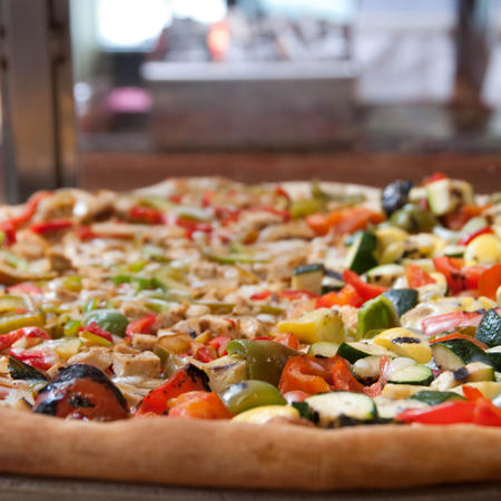Assorted grilled vegetables and chicken on a thin crust pizza