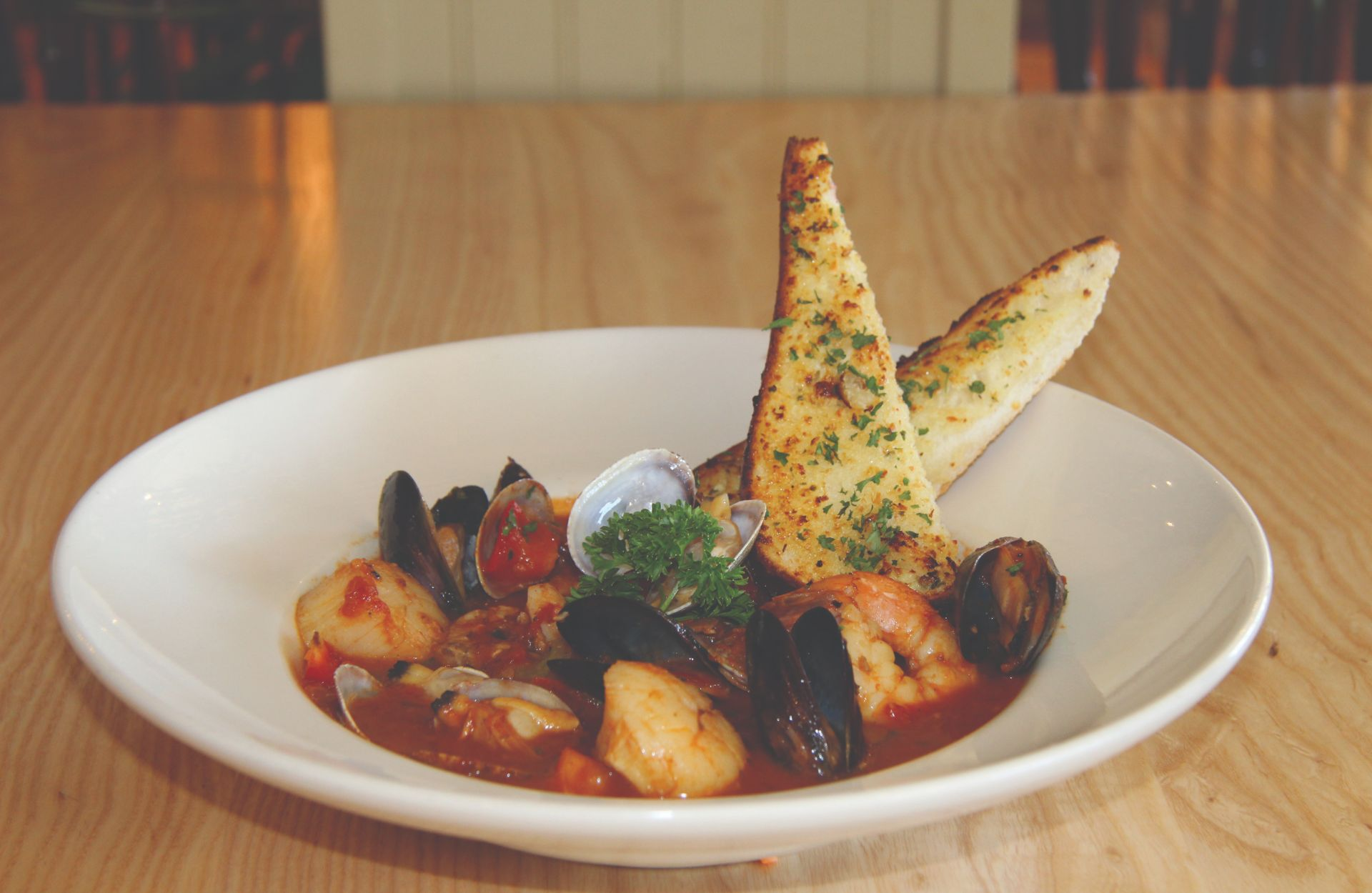 Mussels, clams and scallops in marinara sauce with slices of garlic toasted bread in a white bowl on a wooden table-top
