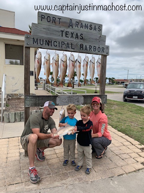 Two adults and two kids holding fishstanding next to Port Aransas TX Sign