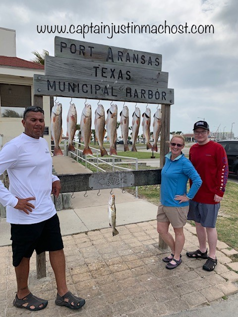 Three people standing next to Port Aransas TX Sign