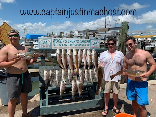 "Three men holding fish next to a board holding fihs that reads ""Woody's Sports Center Port Aransas TX"""