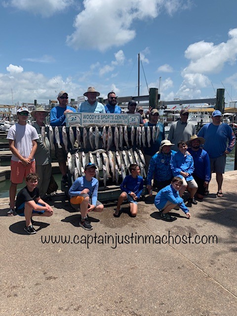 """Large Group of people next to Woody's Sprt Center Sign with a rack of caught fish """"www.captainjustinmachost.com"""""""