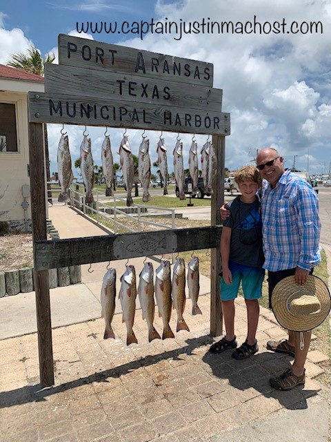 Two people standing next to Port Aransas TX Sign