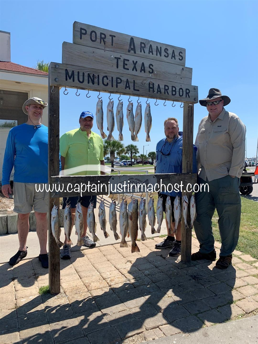 Four males standing around Port Aransa Texas Municiapal Harbor sign with fish hanging from it