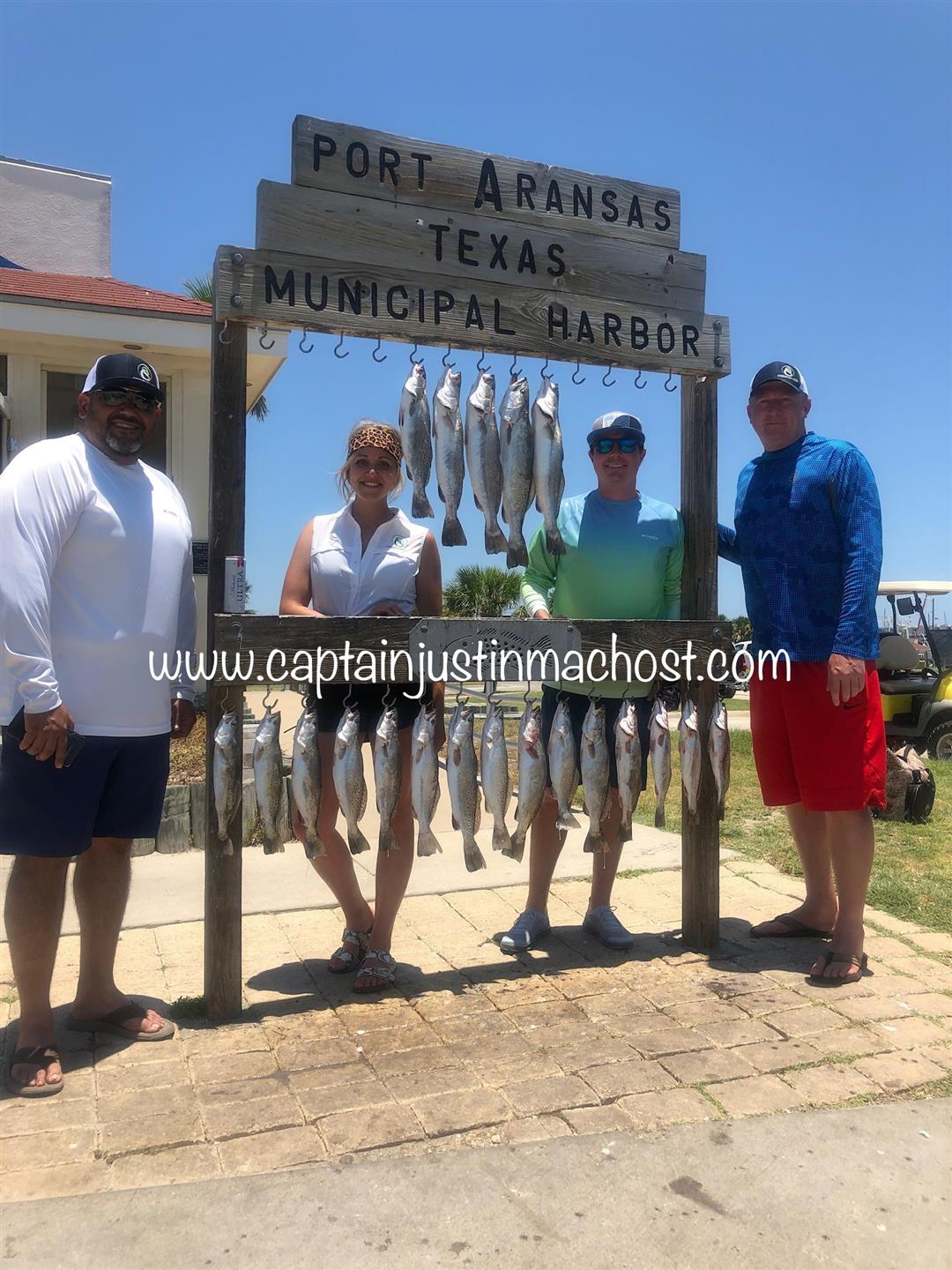 Group of four standing around Port Aransa Texas Municiapal Harbor sign with fish hanging from it