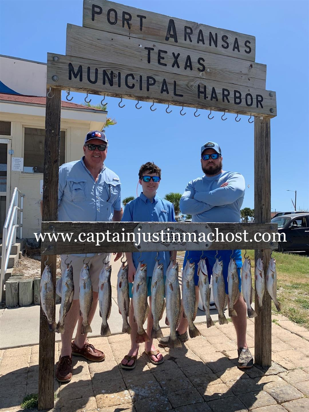 2 Men and a Younger Boy in front of the Port Arkansas Texas Municipal Harbor after fishing