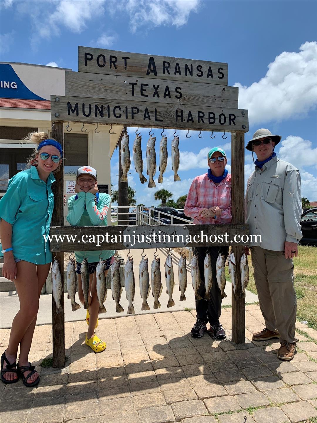 Family of 4 in front of the Port Arkansas Texas Municipal Harbor after fishing