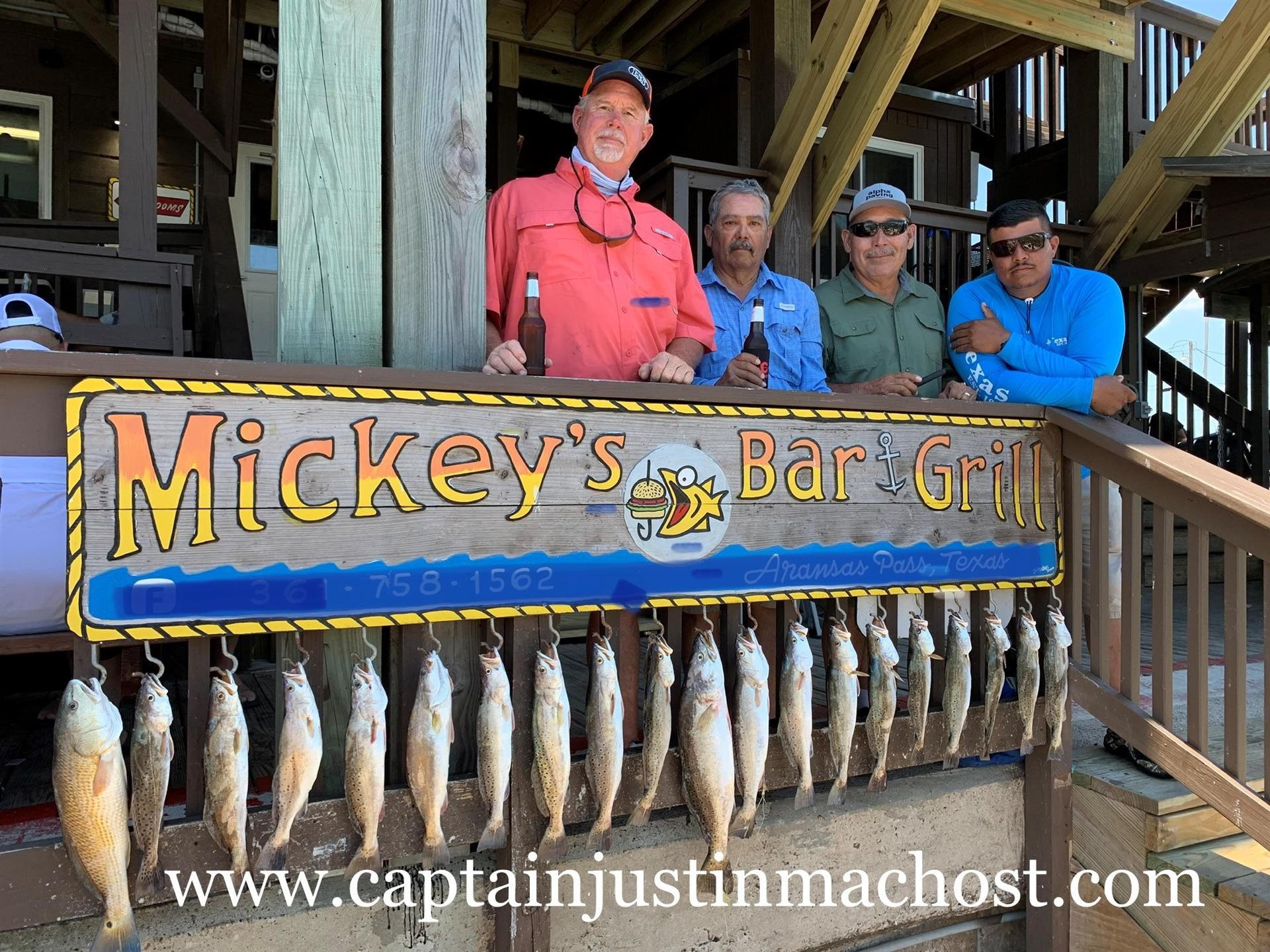 Group of 4 men behind Mickey's Bar & Grill Sign