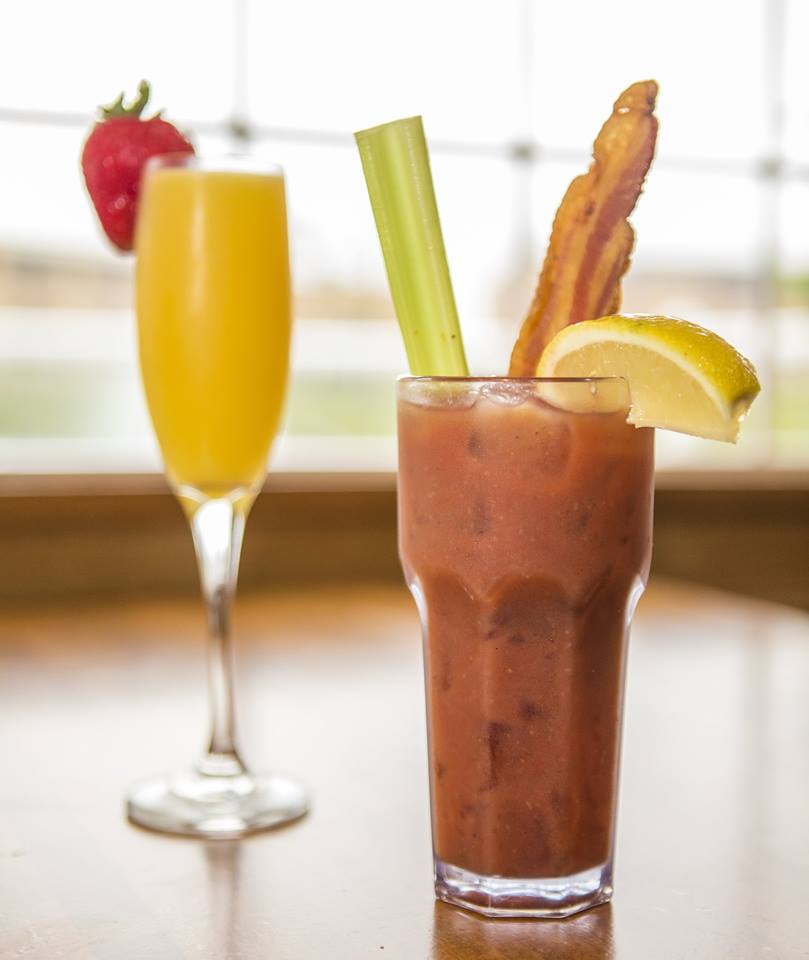 Mimosa in a champagne glass with a strawberry on the rim with a bloody Mary on the side with a celery stick, bacon strip and lemon on the rim