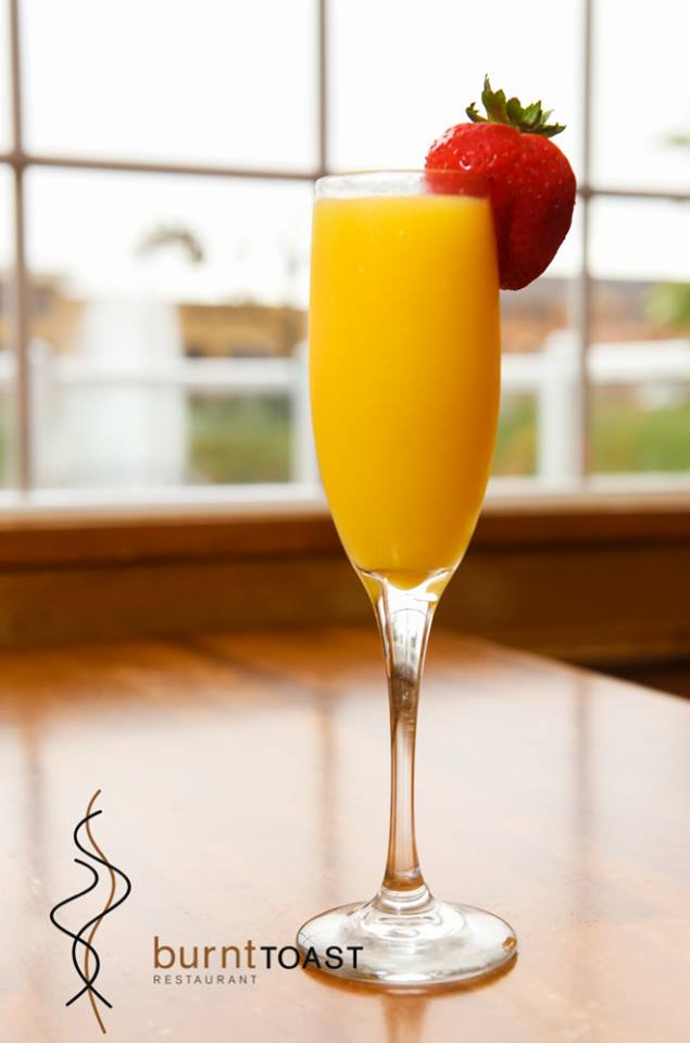 Mimosa in a champagne glass with a strawberry on the rim on a wooden table-top