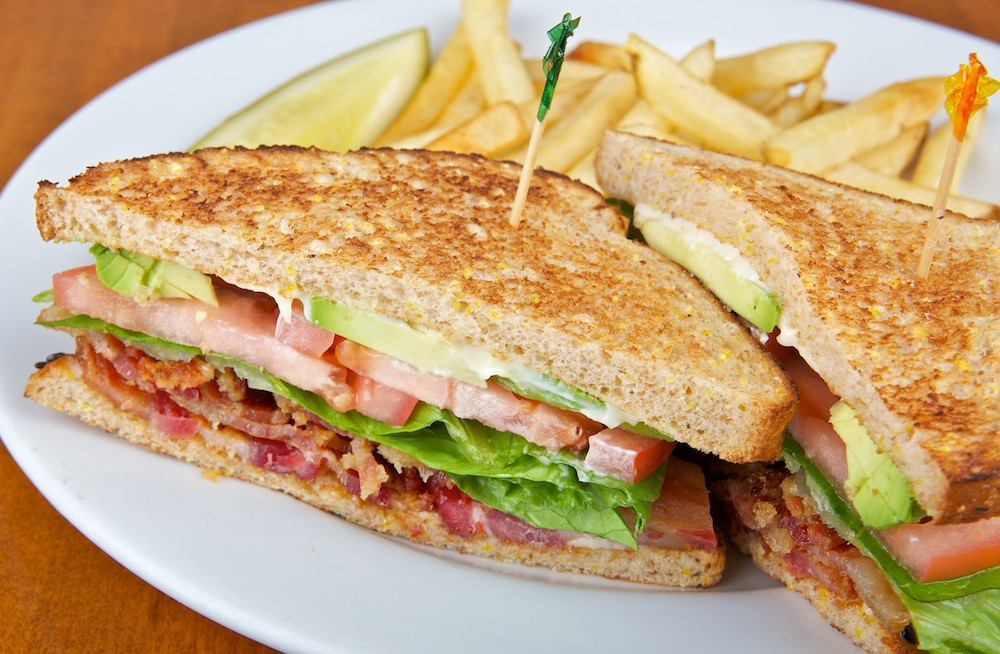 BLT with avocado slices, French fries and a pickle spear