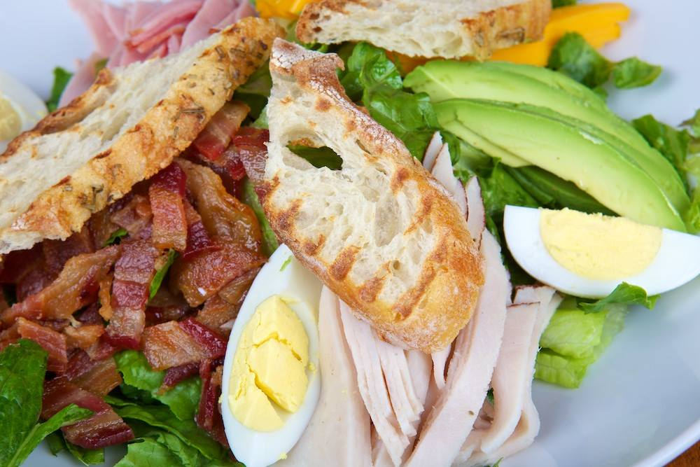 Cobb salad with sliced avocados, hard boiled eggs, chopped bacon, turkey and crustini bread on top