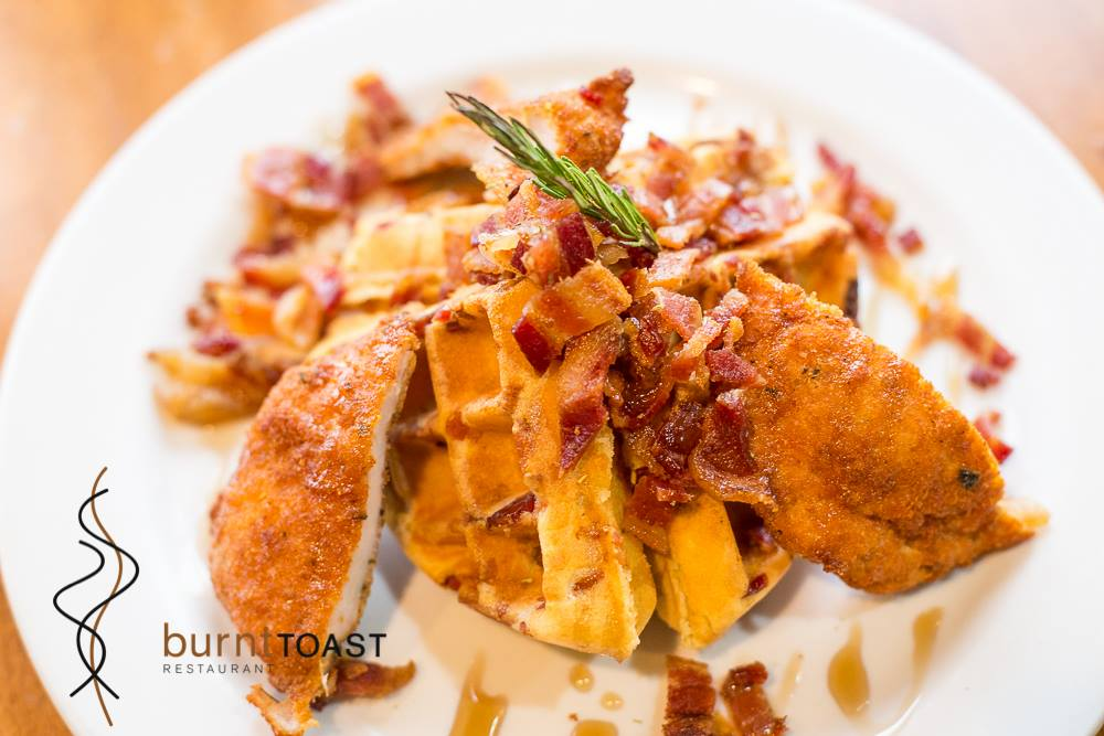 Rosemary chicken over waffles with bacon.